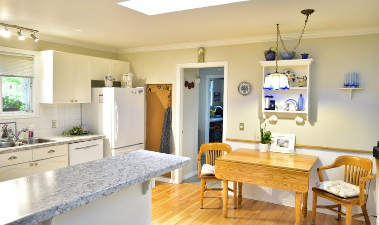 Sunny kitchen with white tiles and cupboards.