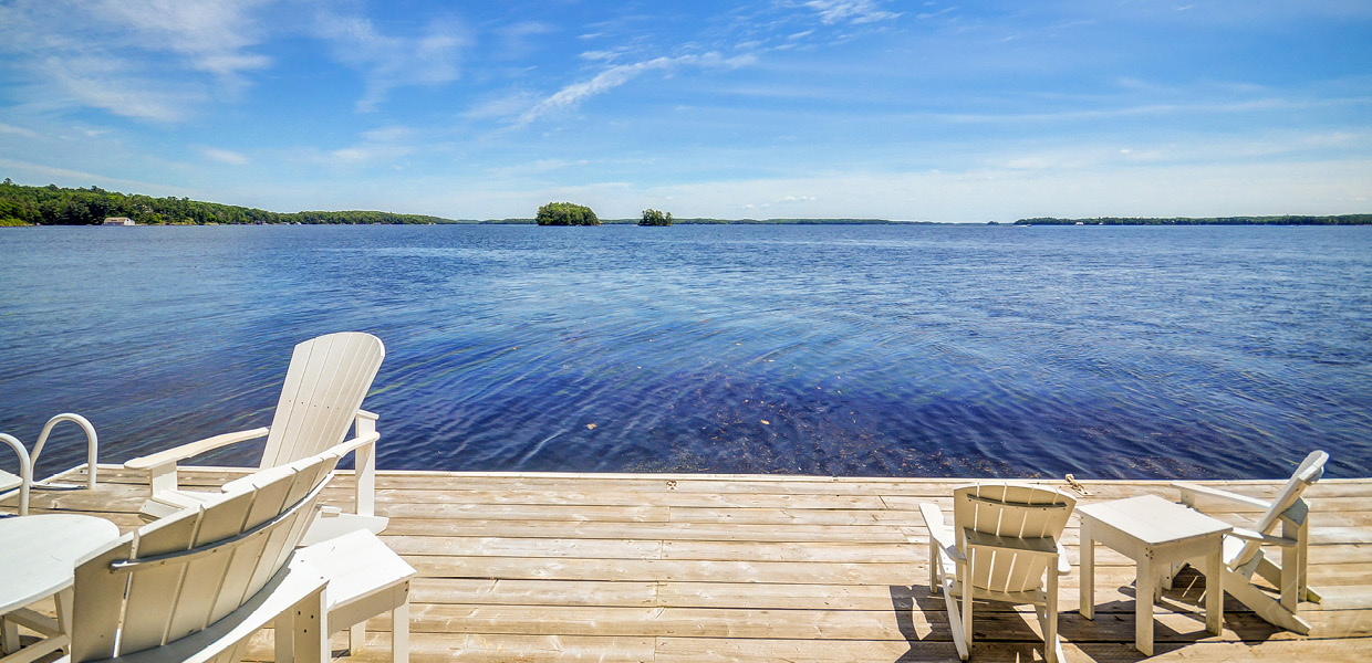 Picture of lake from dock with Muskoka chairs