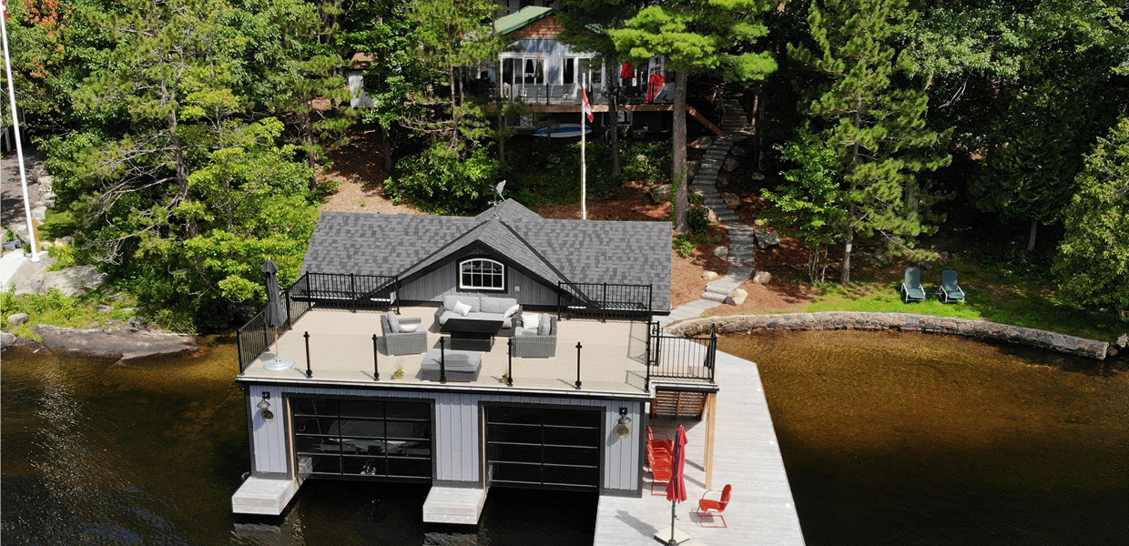 Aerial shot of boathouse wtih sun deck with cottage in background
