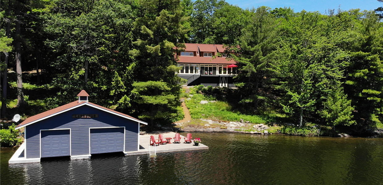 Blue boathouse and cottage with red roof