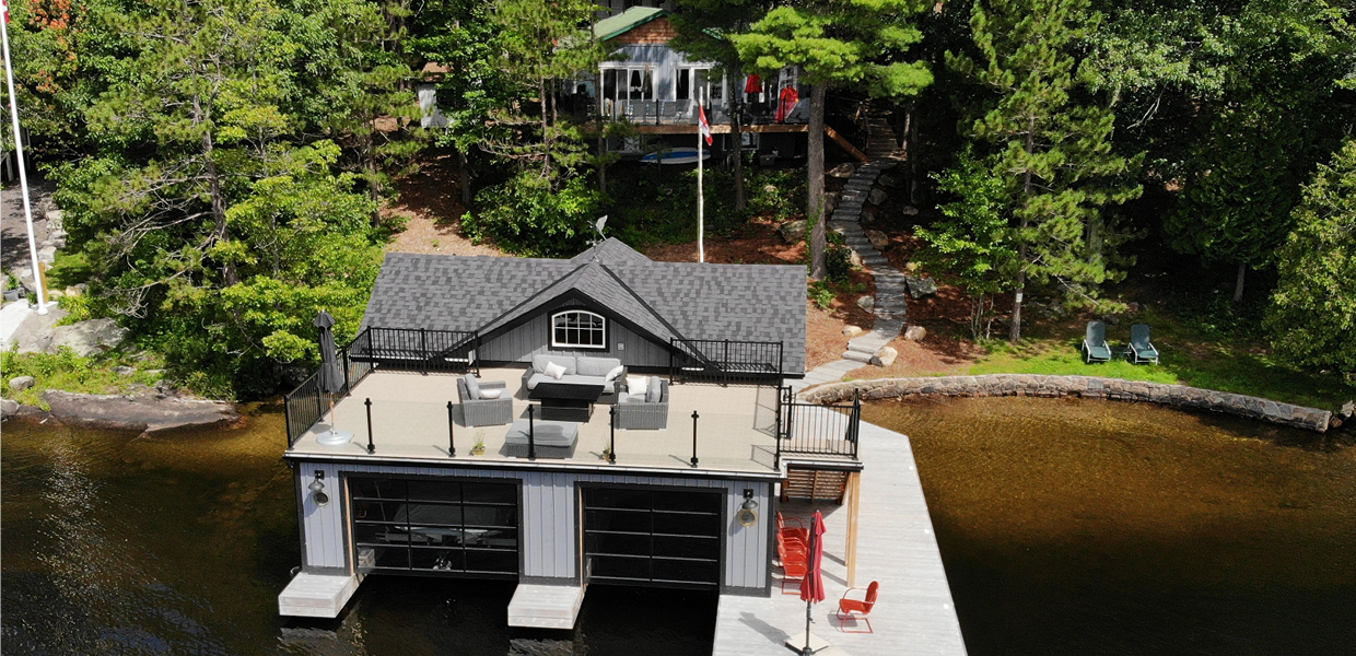 Grey boathouse with sundeck and cottage in background