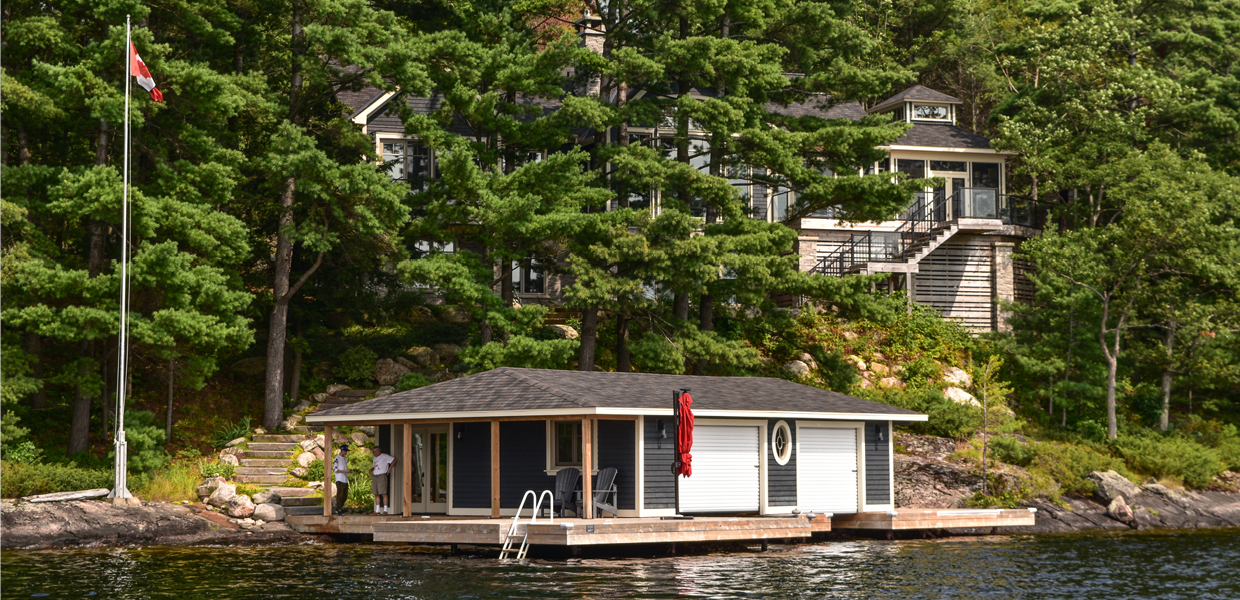 Brown boathouse with cottage behind